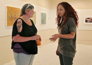 Quaglia captures the attention of CSUEB student Melanie Williams at her campus art show.