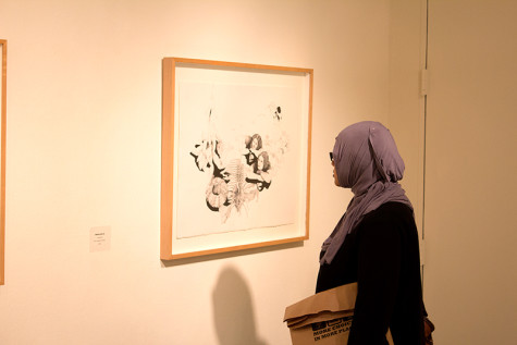An exhibition attendee observes a student's work at Tuesday's reception.