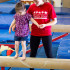 Pacific West instructor helps a young member on the balance beam.