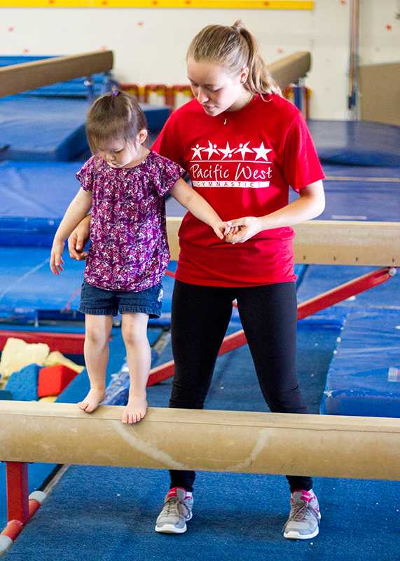 Pacific+West+instructor+helps+a+young+member+on+the+balance+beam.