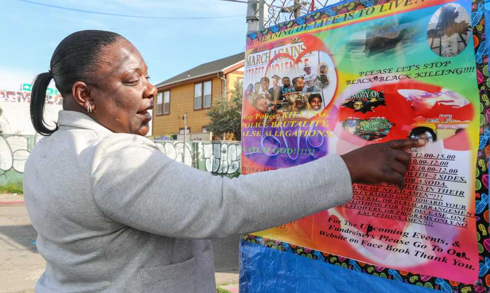 Carol Jones points to the M.O.R.E Foundation sign on the corner of Chestnut Street and 34th Street in West Oakland, on Saturday, March 14.