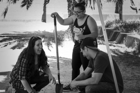 Grad student and squad lead Ashley Schmutzler, left, sits back and cracks jokes with her team Vanessa Armenta, center, and Michael Pacma, right, during a short rest after digging at their sites.