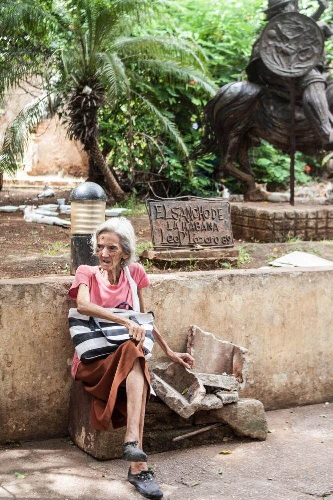 A+woman+rests+on+a+crumbling+stone+bench+next+to+a+statue+in+Old+Havana.