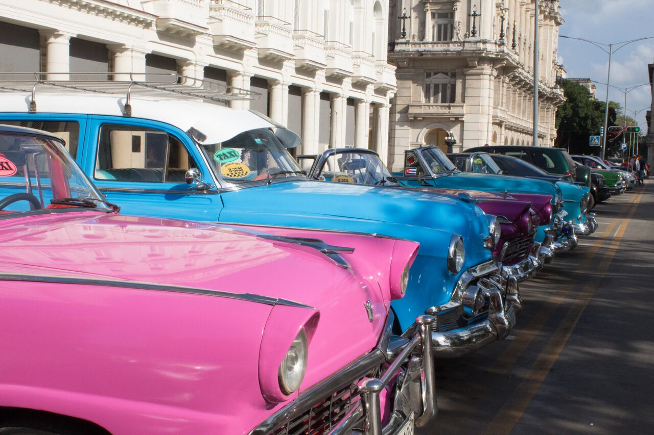A+line+of+taxis+are+parked+on+the+street+in+Old+Havana.