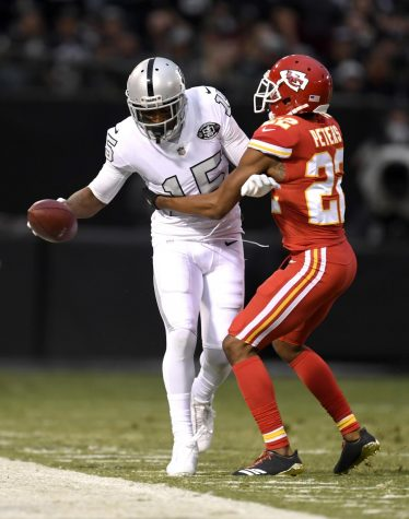 Oakland Raiders wide receiver Michael Crabtree (15) is pushed out of bounds by Kansas City Chiefs cornerback Marcus Peters (22) after making a catch in the first quarter at the Coliseum in Oakland on Thursday, Oct. 19.