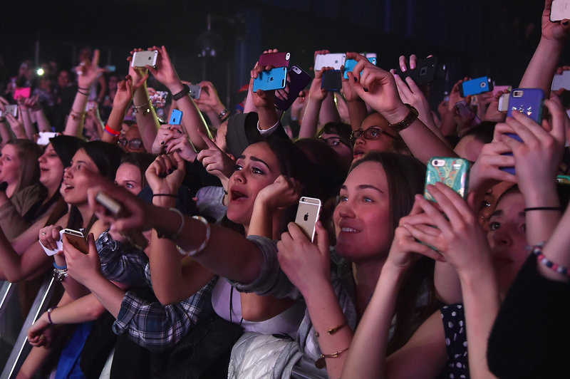 Concertgoers use their cellphones during a Fifth Harmony concert March 23, 2015, in New York. The company Yondr created a locking pouch to hold phones during performances, creating a