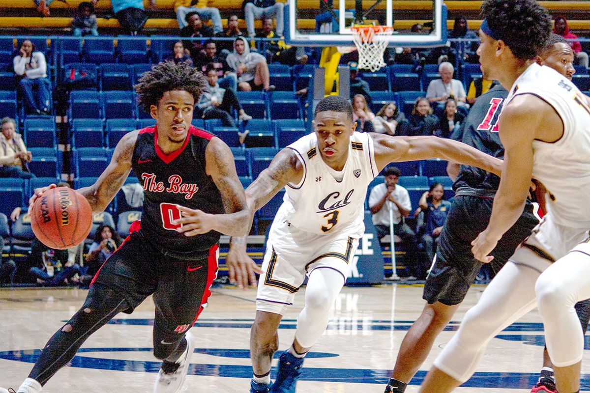 Cal State Eastbay junior guard Juwan Anderson dribbles across his opponent during the game against Cal Golden Bears.