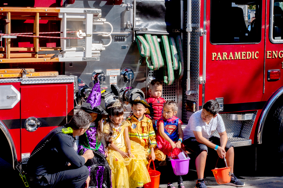 A+Hayward+Firefighter+gets+ready+to+take+a+picture+with+a+group+of+kids+dressed+for+the+occasion.
