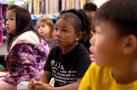 Kindergarten is the first year for children to learn the behavior expected in school. Phoebe (left), age 5, and Nala (center), age 5, listen attentively to their teacher at the front of the room.