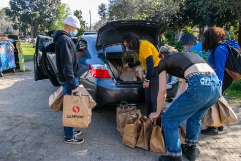 Local volunteers begin unpacking food for the houseless living at People's Park in Berkeley, California, on March 5. The event was put on by the Liberated Lens Film Collective, Food Not Bombs, and National Public Housing Museum in collaboration with Omni Commons, a community event space.