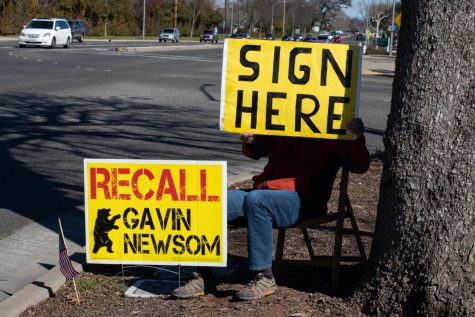 "A 63-year-old local man, who goes by the name of Al, sits on the side of the road holding a poster that says 'sign here,' conveying to passersby that they can partake in signing the petition in the nearby parking lot. Al confessed that he works with ""a lot of crazy liberals"" and fears being identified and/or harassed for his political views."