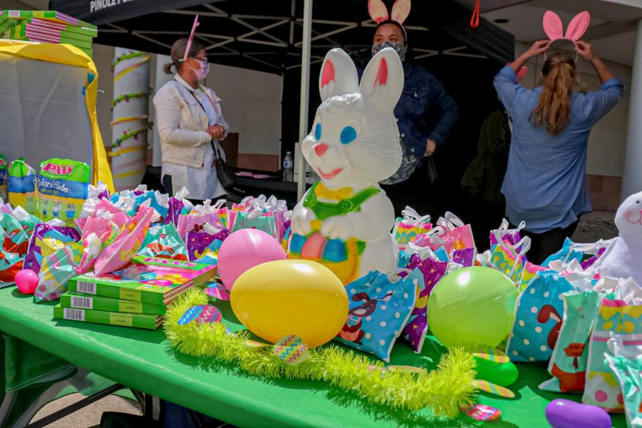 """Volunteers for Pinole's """"Drive-Thru Spring Eggstravaganza"""" hosted by the Pinole Police Department add the finishing touches for the goody bag booth on April 3."""