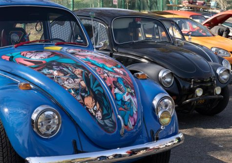 These buggies are one of a kind. The blue Volkswagen (VW) Beetle on the left totes a hand-painted cartoon design of famous characters on its hood along with multiple other unique customizations.