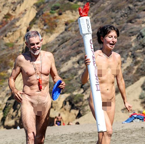 George Davis and Gypsy Taub carry the torch for the 2014 Nude Olympic Games at Baker Beach in San Francisco earlier this month.