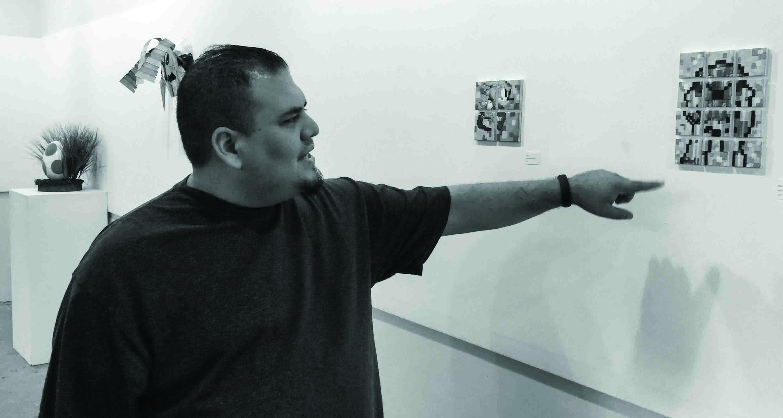 Senior Art student Robert Marrojo showcases his 8-bit style painting on Monday at the Kiln Gallery.