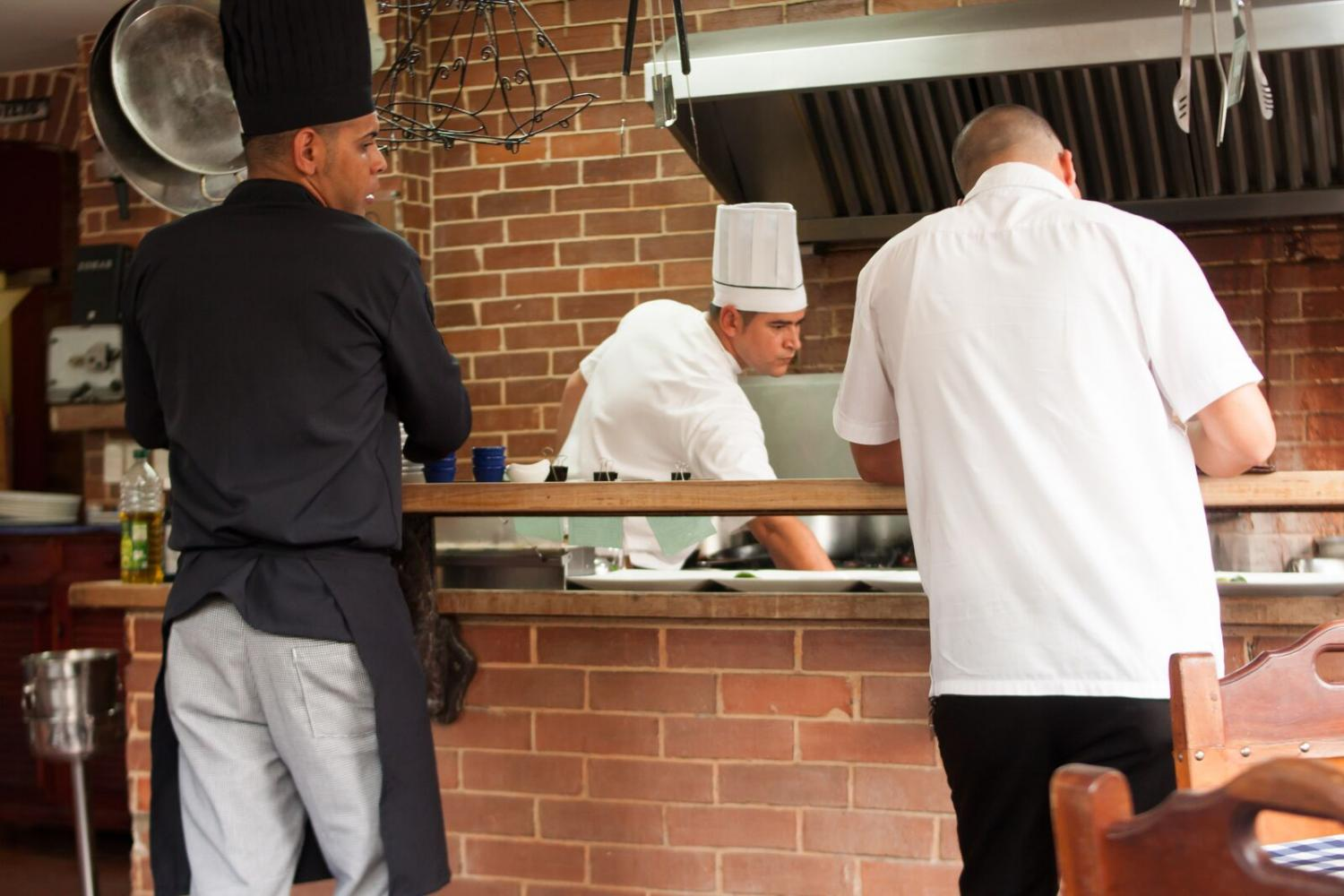 Chefs+and+a+waiter+prepping+plates+to+deliver+to+customers+eating+at+El+Idilio.
