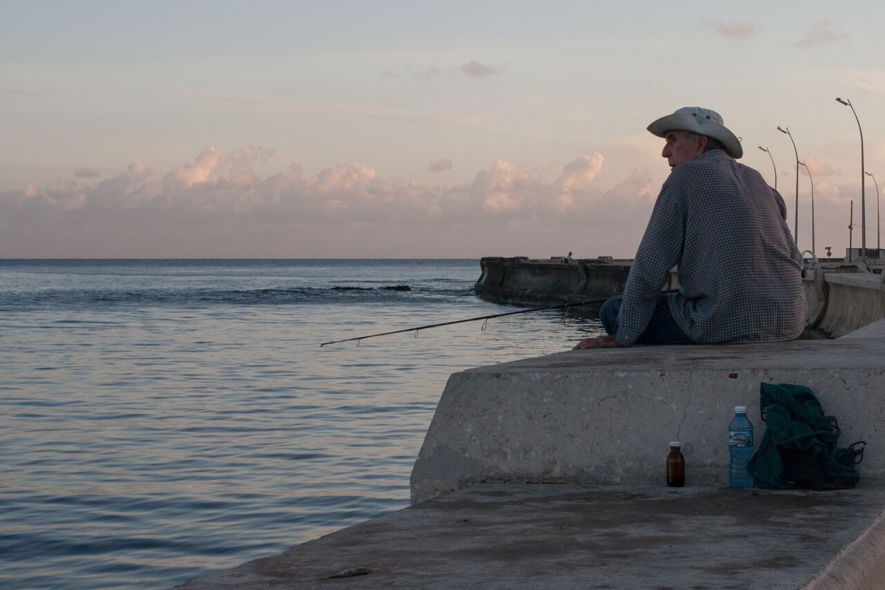 An+elderly+man+gazes+over+the+horizon+while+patiently+waiting+to+catch+his+next+fish.