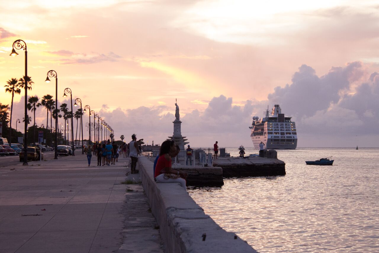 A+cruise+ship+departs+Havana+as+locals+sit+around+and+watch.+