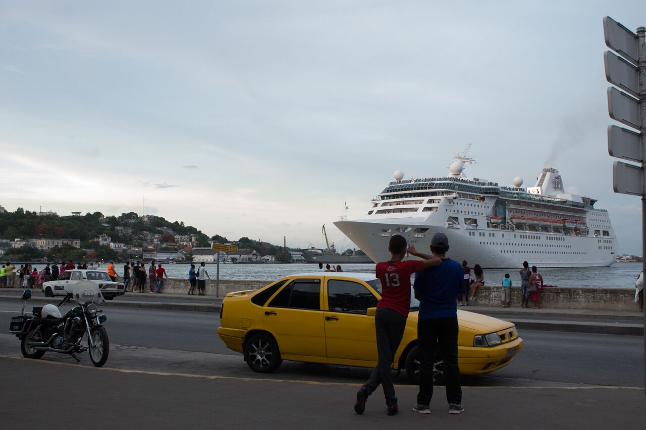 Locals+watch+as+a+cruise+ship+leaves+the+port.