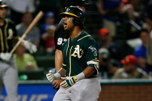 Oakland Athletics Khris Davis celebrates as the crosses home after hitting a three-run home run in the 10th inning of the team's baseball game against the Texas Rangers, Tuesday, July 24, 2018, in Arlington, Texas. The A's won 13-10.