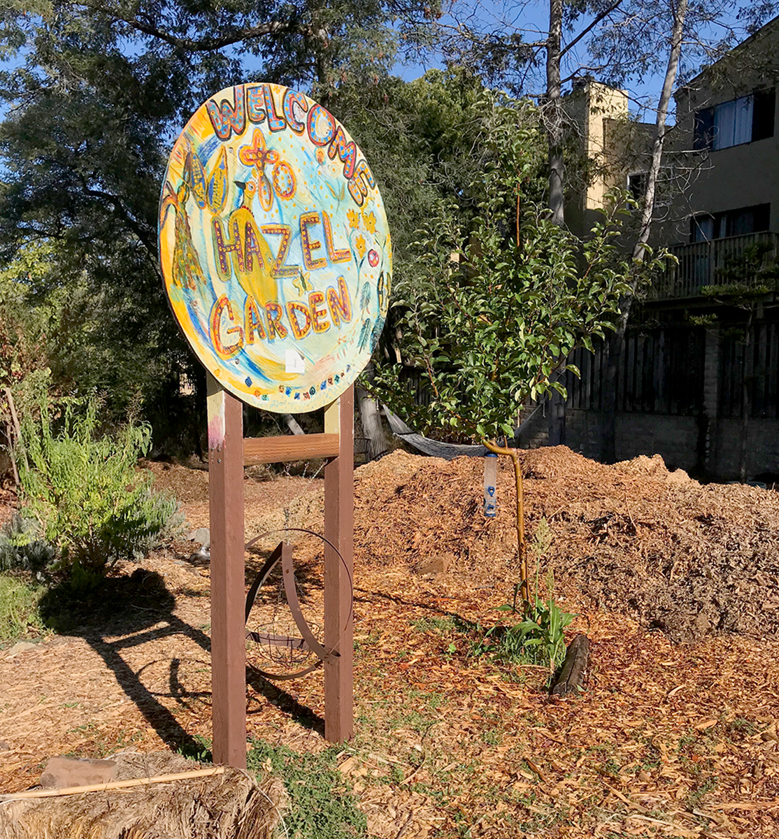 ABOVE: A handmade signs designates the area and welcomes patrons to the Hazel Garden. BELOW: Benjamin Collier watering the plants at his community garden.