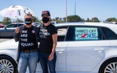 """Karen SchulerHill (left) and Karen Rasmussen (right) stand outside their car, decorated with their voting sign to participate in the """"votercade"""" at the Bay Area John Lewis Voting Rights Day of Action at the Oakland Coliseum on May 5."""