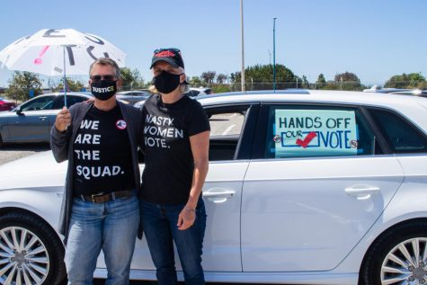 "Karen SchulerHill (left) and Karen Rasmussen (right) stand outside their car, decorated with their voting sign to participate in the ""votercade"" at the Bay Area John Lewis Voting Rights Day of Action at the Oakland Coliseum on May 5."